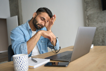 Man rubbing his eyes while sitting at the computer