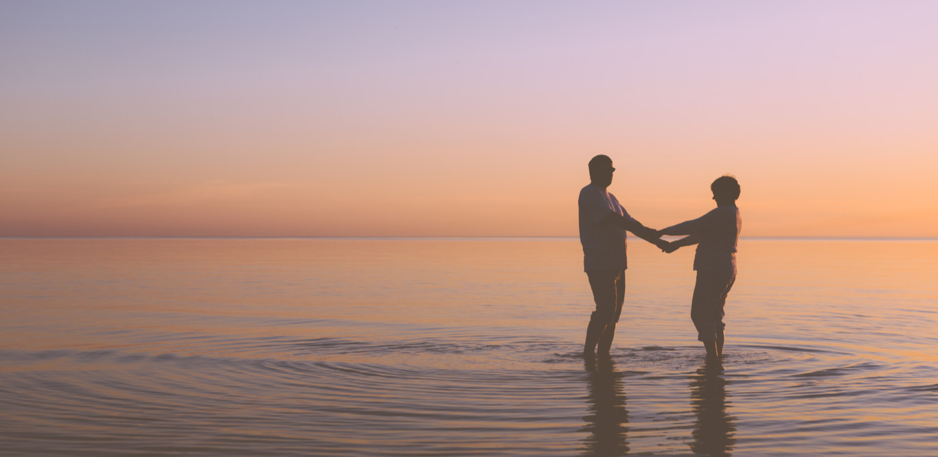 Older couple standing in the ocean at sunset