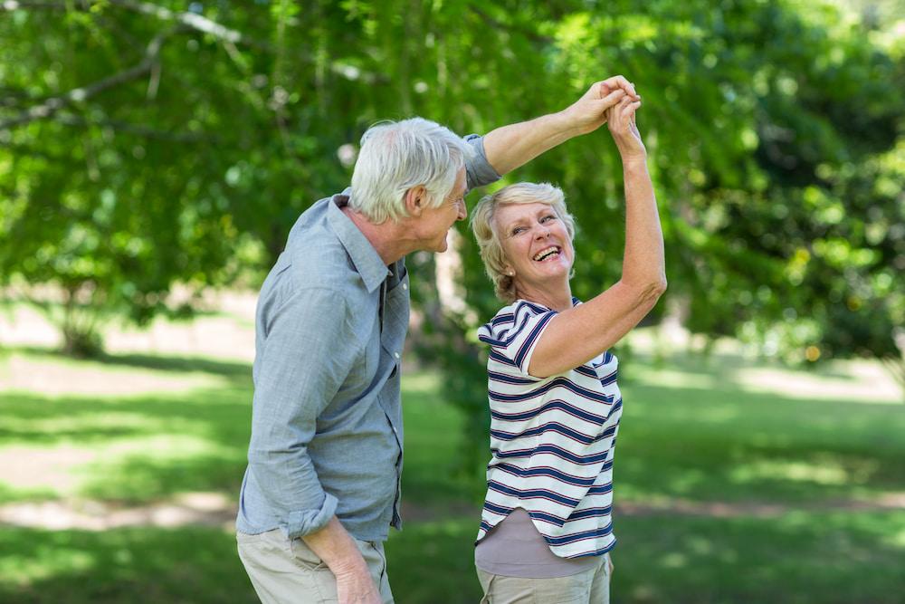 Older couple dancing in the garden happily