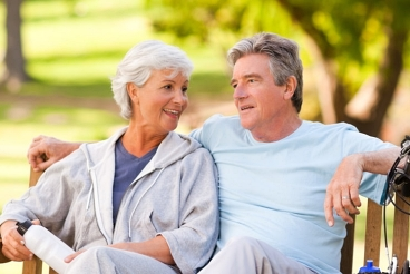 Middle aged couple taking a break on a park bench during a bike ride