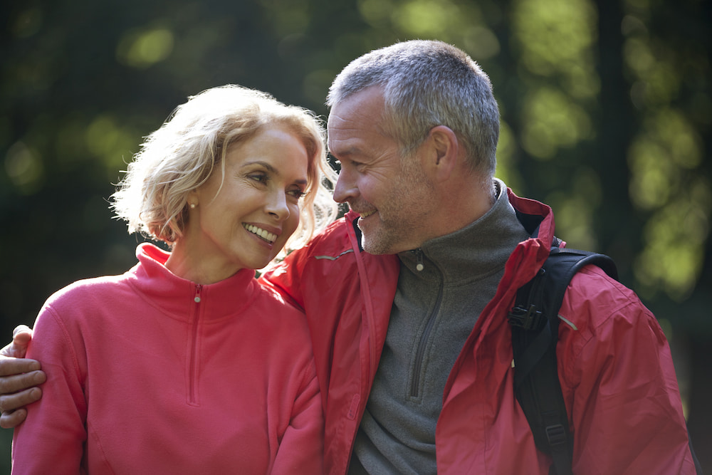 Older couple huging and smiling while hiking