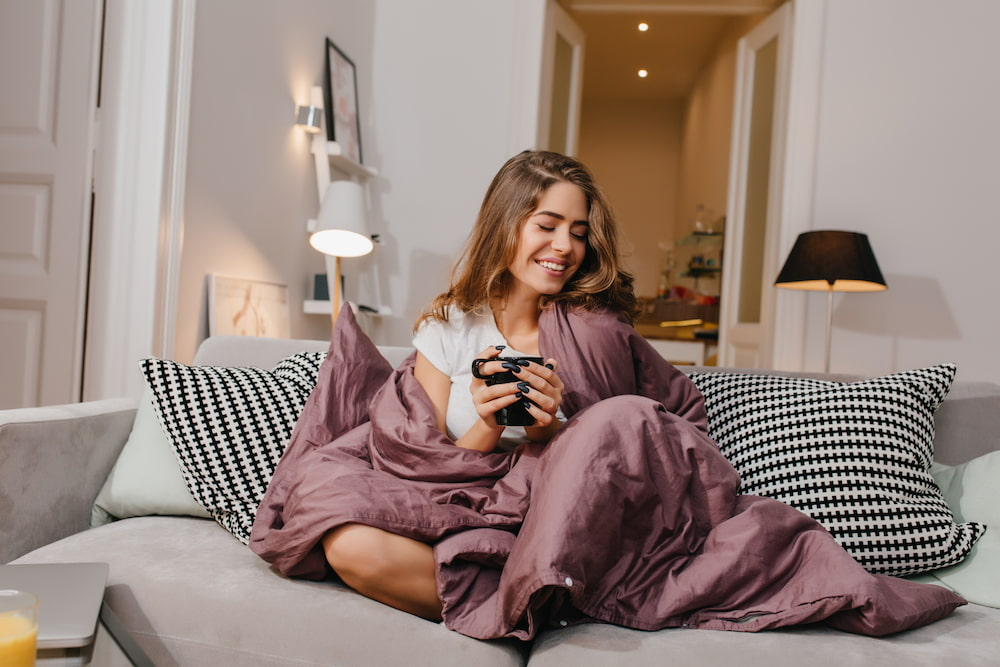 Young woman comfortably recovering on the couch under a blanket