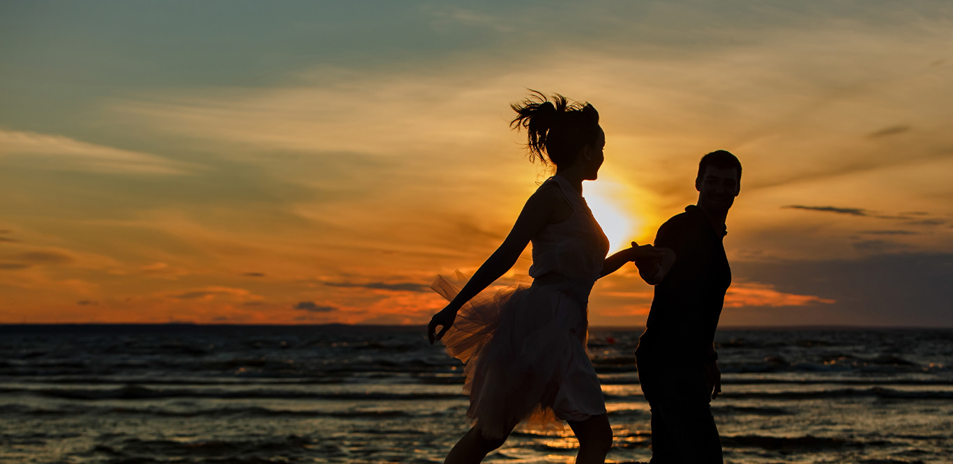 Young couple holding hands on running on the beach at sunset