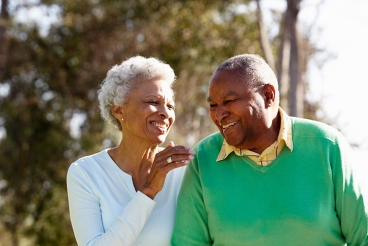 Older couple smiling as they walk outside
