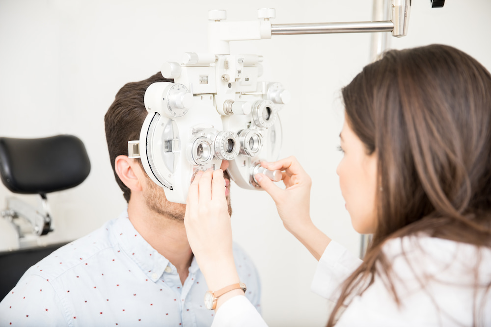 Young man receiving an eye exam from a female doctor